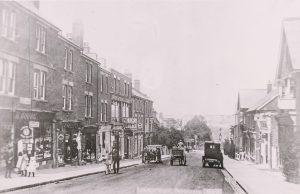 Early car parked on London Road, opposite a motor garage